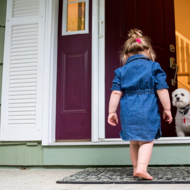 Rear view of young girl walking towards open door with dog waiting