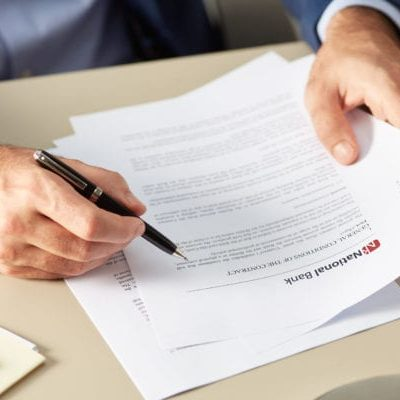 Faceless businessman holding pen while reading thoroughly bank contract
